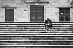 alone (trazmumbalde) Tags: street santiago bw stairs spain pessoas waiting europe alone doors sitting galicia santiagodecompostela rua escadas nikonstunninggallery challengeyouwinner
