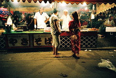 mr. and mrs. yukata get a fried thing (troutfactory) Tags: street food film festival japan night lomo lca eating cook stall rangefinder yukata osaka vendor analogue kansai matsuri tenjin 2007 natura1600