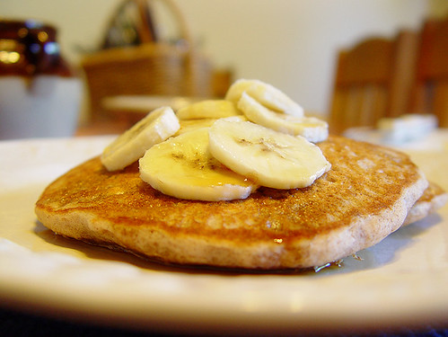 Cinnamon Vanilla Hazelnut Pancakes garnished with sliced banana and 100% pure maple syrup