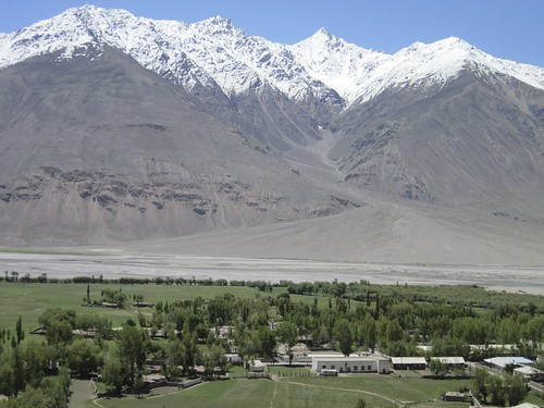Village and snow-capped mountains in Panj river valley, Tajikistan