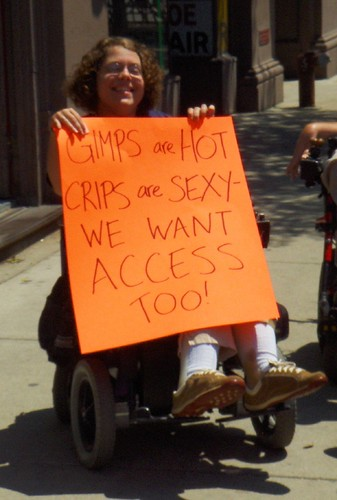 Gimps are HOT!: A powerchair user at an ADAPT action holds up a sign saying 'Gimps are hot! Crips are sexy! We want access too!