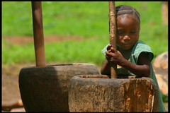 little girl pounding rice (LindsayStark) Tags: africa travel portrait girl children war sierraleone conflict humanrights humanitarian displaced idpcamp refugeecamp idps idp humanitarianaid emergencyrelief idpcamps waraffected