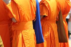 saffron robes with bags (basketgirlsteph) Tags: orange temple robe buddhist religion monk parade monks saffron watlaobuddhavong