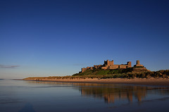 Bamburgh Castle (fuerst) Tags: greatbritain travel blue sea england reflection castle beach strand dawn coast meer northumberland northsea dmmerung blau schloss bamburgh nordsee spiegelung ferien burg reise kste flickraward grosbritannien canoneos1000d flickraward5