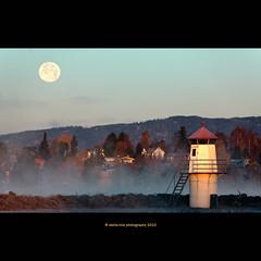 moonset (stella-mia) Tags: morning moon lighthouse mountains cold norway fog sunrise frost explore frontpage moonset hamar mjøsa 70200mm coldair morningfrost bythelake explored extenderef2xii canon5dmkii lakemjøsa frosttåke bestcapturesaoi elitegalleryaoi annakrømcke tjuvholmenhamar