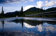 The Glenn Highway (code poet) Tags: road trees sky mountain reflection water topv111 alaska clouds landscape puddle topv555 topv333 pavement bubbles 100v10f topv777 rv guardrail matsu 1022mm