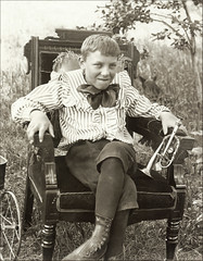Victorian Boy with Toy Horn (newmexico51) Tags: old boy smile wheel vintage wagon toy chair backyard shoes child boots antique stripes spokes 19thcentury victorian tie clothes horn nineteenthcentury tinhorn