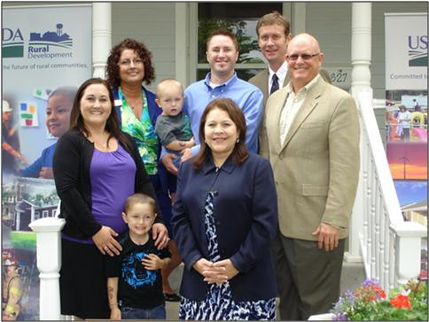 Daniel and Season Brown and their sons Jack and Cash fully enjoy their home, purchased through the USDA Rural Development Single Family Housing Direct Loan Program, In Holton Kansas. From Left to right front row Season Brown, Homeowner with son Jack; Rural Housing Service Administrator Tammye Trevino; and Roger Hower, Kellerman Real Estate (Back row) Elda Reader, USDA Rural Development Area Specialist, Manhattan Office; Daniel Brown, Homeowner with son Cash; and PJ Neary, USDA Rural Development Area Director, Manhattan Office.