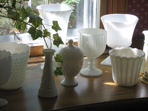 Collection of white milk glass on sideboard beneath window lets the light through the glass, via Flickr: caroll.mary