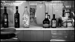 Window shopping at Tosi & Co. (Eric Flexyourhead) Tags: street city urban bw canada window glass shop vancouver reflections blackwhite store mainstreet chinatown bc display britishcolumbia tomatoes storefront angelo 169 balsamicvinegar balsamico cannedgoods acetobalsamico tosico olympusep1 pentax11018mmf28 tosiitalianfoodimportcompany plumtomotoes