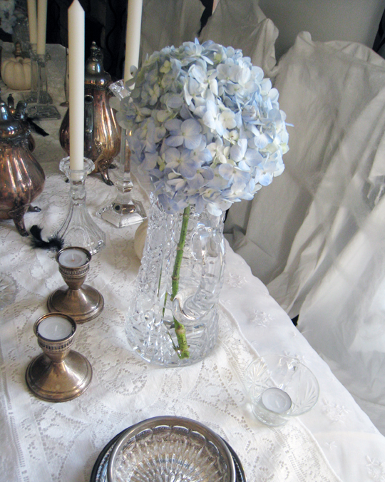 blue hydrangeas in vintage crystal pitcher+tarnished silver candle holders+silver tea set+halloween table top+table decorations