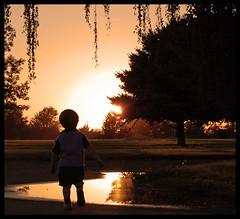 childhood summer... (kalurah) Tags: park trees boy sunset sky orange sun reflection water silhouette dark shadows child dusk outline wallawalla d40 nikond40