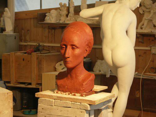 Sculpture en terre figurative vue de face représentant la tête d'une femme avec les cheveux tirés en arrière et retenus par un serre-tête recouvert de tissu d'après une peinture de Bronzino – Sandrine Vallée