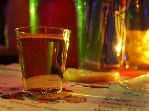a shot of tequila sitting on the bar in a colorful setting
