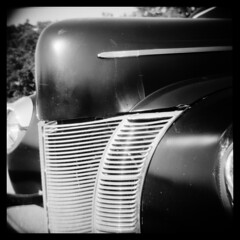 Deluxe No.4 (Ralph Krawczyk Jr) Tags: morning trees light shadow summer sky blur 6x6 sunshine metal vintage mediumformat reflections outside nose classiccar toycamera lofi highlights bumper chrome squareformat worn diafine hood grille swank frontend holga120n driverside flatblack aristaeduultra100 ralphkrawczykjr wixommichigan 1940forddeluxecoupe