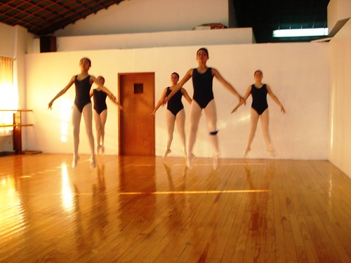 Ballet students jump into the air in class