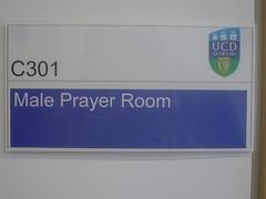 لافتة مكتوب عليها 'C301 - Male Prayer Room' و عليها شعر كلية جامعة دبلن