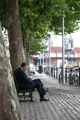 Lunch break (Matthew Sylvester) Tags: trees businessman bench bristol newspaper sandwich cranes bicycles suit cobbles quayside floatingharbour shinyshoes