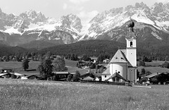 Picturesque (ronet) Tags: blackandwhite bw mountain alps slr film church geotagged austria meadow scan pentaxist agfaapx100 ilfotecddx developedmyself wildenkaiser diydeveloped