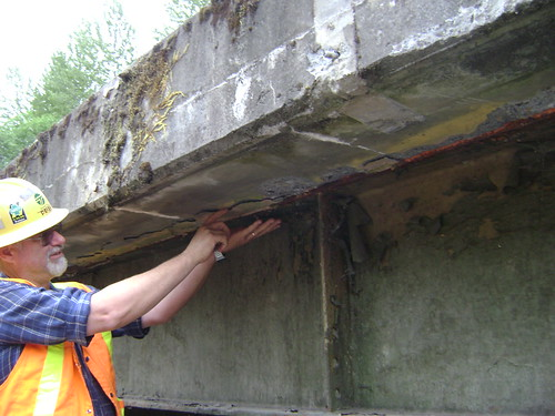 A bridge inspector checks the integrity of the concrete in a bridge in Washington State.
