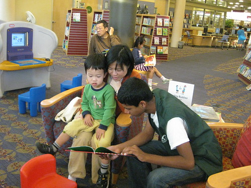 A Reading Buddy teen volunteer reading from a book to a boy who is sitting on his mother's lap in the Children's Area of Almaden Library