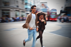A couple crossing the Oxford street (Che-burashka) Tags: street people urban motion blur london buses girl smiling youth happy blurry couple candid indian happiness places running rush oxfordstreet youngman londonist ef28mm canonef28mmf18usm urbanlyric
