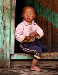 Bhutanese boy (edwindejongh) Tags: boy portrait asian kid bhutan flies portret bhutanese jongetje vliegen doorpost deurpost superaplus aplusphoto traingsbroek