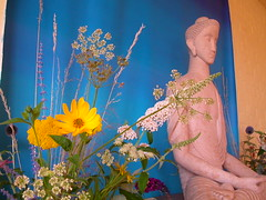 Taraloka Buddha and flowers on shrine