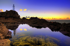 Two lonely clouds at the lighthouse (Corica) Tags: uk greatbritain blue sunset sea lighthouse seaweed reflection water clouds landscape rocks britain jersey hdr channelislands rockpool corbiere sigma1020mm stouen polariser photomatix stouens stbrelade corica corbierelighthouse canon400d superaplus aplusphoto