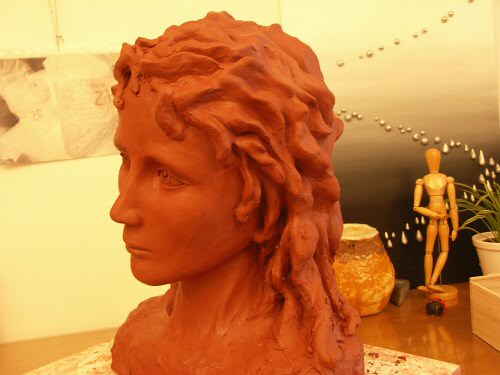 Sculpture en terre figurative vue de 3/4 représentant la tête légèrement inclinée d'un jeune homme aux cheveux longs et ondulés avec une expression à la fois rêveuse et triste – Sandrine Vallée