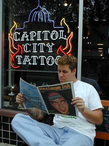 Brian, owner of Capitol City Tattoos on Willy St. in Madison holding a