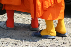 tradition meets practicality (basketgirlsteph) Tags: orange temple robe sandals buddhist religion monk tights nike parade monks flipflops saffron birkenstocks watlaobuddhavong