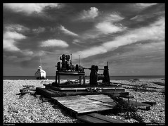 Dungeness Beach (lowbattery) Tags: sky blackandwhite bw white black beach water clouds boat stones dungeness romney romneymarsh