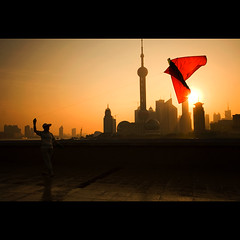early bird. (chris spira) Tags: china street morning people kite bird senior skyline sunrise wonderful early mood moody shanghai chinese scenic atmosphere explore lonelyplanet pudong cinematic kiteflying bund jinmao tvtower nationalgeographic shilouette thebund orientalpearltower energetic