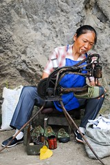 Cobbler's (5ERG10) Tags: china street portrait people woman face sergio rock shirt lady bag tin person shoe 50mm countryside concentration eyes nikon strada village hand serious market expression cigarette candid sewing country machine august can tools apron fabric mano  nikkor f18 stool guizhou mercato checkered ritratto cina cobbler shoemaker 2010  faccia lattina d300 concentrated bootmaker villaggio repairer calzolaio zunyi sgabello  checquered macchinadacucire ciabattino cucitrice amiti punteruolo 5erg10  maoshi