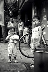one summer morning. (theshanghaieye) Tags: china street summer urban blackandwhite tree bike bicycle kids children kid interestingness alley asia child shanghai drink monotone icedtea explore   shanghaiist frenchconcession longtang nongtang  middlekingdom