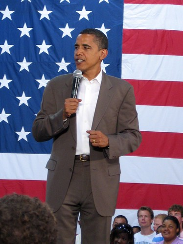 President Obama, sans tie, speaking in front of a large American flag