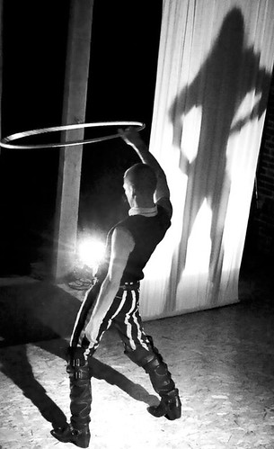 Black and white photo of a person with a shaved head, wearing a white shirt with a black vest, tight black-and-white striped pants, and knee-high black leather boots. They are holding a hula hoop over their head, while the shadow of an apparently long-haired person is cast on a white curtain near them.
