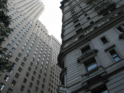 Looking up at two large art-deco style Wall St buildings.