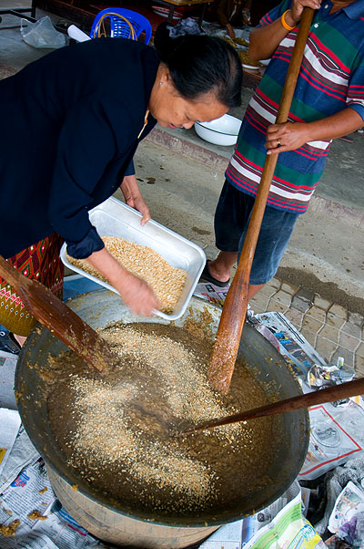 Adding peanuts to khao ya koo, sweet sticky rice, Mae Hong Son