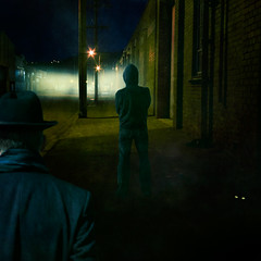 Under surveillance (borealnz) Tags: street light mist man texture hat youth night scarf cat buildings square lights hoodie eyes streetlight darkness pavement ominous foreboding surreal eerie powerpole footpath watched following watcher manray bsquare artlibre flypapertextures borealnz thankstopaulgrandforthehoodie
