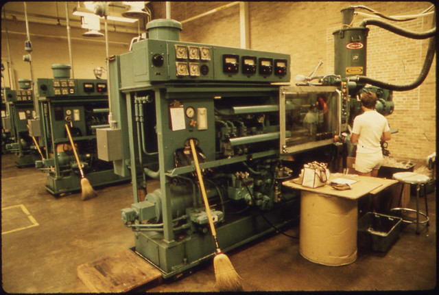 Interior of the 3m Co(Minnesota Mining and Manufacturing) Plant Showing a Machine Being Monitored by an Employee by The US National Archives