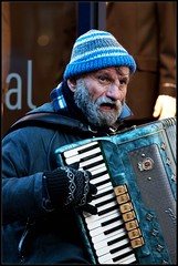 The street musician. (B.Jansma) Tags: street portrait musician playing man cold male netherlands canon shopping beard outside blauw adobephotoshop dof bokeh lol candid details nederland center bleu gloves cap instrument portret muts lightroom streetshot straat koud spelen 500d baard muzikant mutsje handschoenen leidsehage weetdenaamvanhetinstrumentnietmeerp canon70200mmlf4isusm manwithbeards
