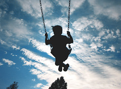 Swinging in the Sky (McMorr) Tags: blue boy sky white black playground clouds interestingness child country swing treetops explore 31 cirrus sihlouette creativenonfiction mcmorr