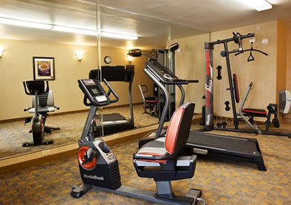 Fitness center with cardio equipment by Comfort Inn and Suites San Bernardino CA