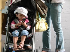 Toddler with mobile phone (Leonard John Matthews) Tags: street concentration focus toddler phone contemporary sydney australia jeans mum plans pram assertive eoshe independentphotos humanhunt
