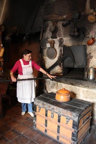 Doña Herminia de pie, con pala, frente al horno