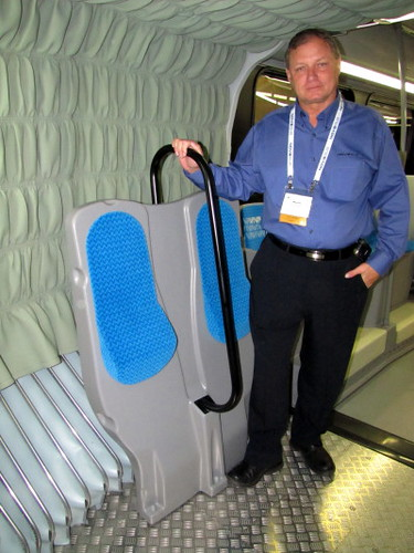 Wayne Feagan of Nova Bus shows standing stall inside his company's 60 ft long articulated bus. Trans-Expo 2010 Shows Hybrid Diesel-Electric, GPS, Wi-Fi, Solar-Power & H.264 Technologies in Public Transit Buses