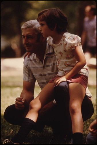 > Father and Daughter Enjoying the Fourth of July Holiday While on a Picnic in a Park at Sleepy Eye, Minnesota...
