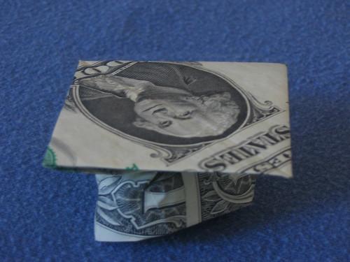 Photo eines aus einer Dollarnote gefalteten Doktorhuts